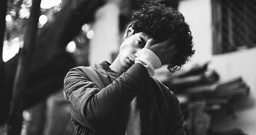 people grayscale photo of man in jacket putting his palm on his forehead human