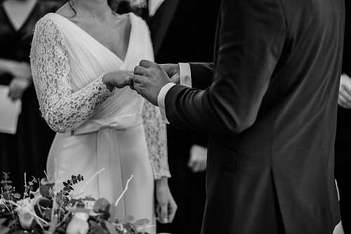 person grayscale photo of man insert ring into woman during wedding ceremony human