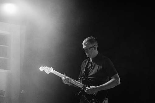 person grayscale photo of man playing guitar people