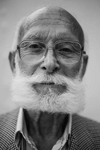 people grayscale photo of man wearing eyeglasses human