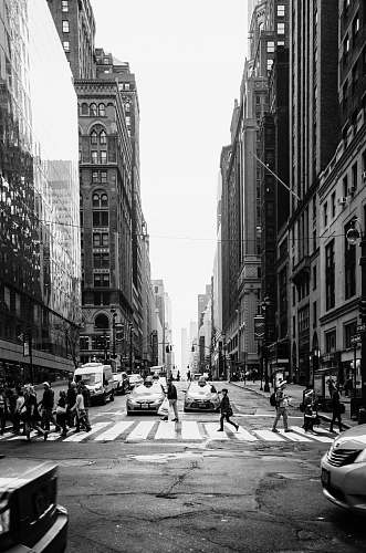 person grayscale photo of people crossing the road road