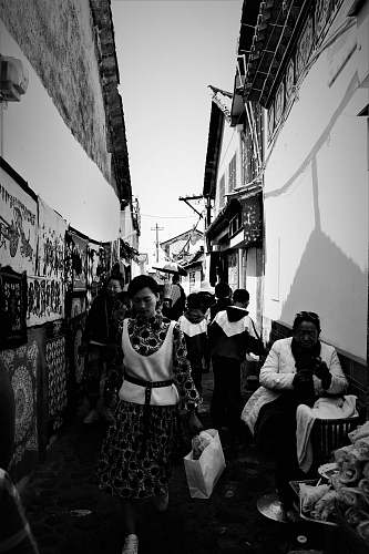 human grayscale photo of people near houses person