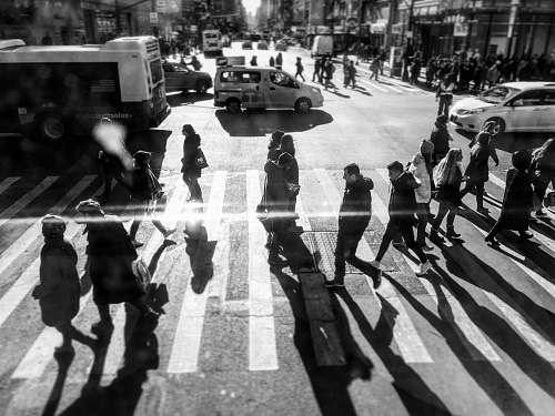 human grayscale photo of people passing by on pedestrian lane during daytime person