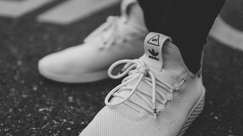 grey grayscale photo of person in white adidas low-top sneakers shoe