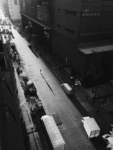 city grayscale photo of person walking on road outside building building
