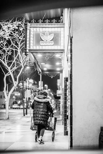 human grayscale photo of person walking on sidewalk near Adidas store people