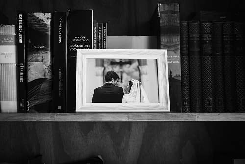 human grayscale photo of photo frame on wooden shelf book