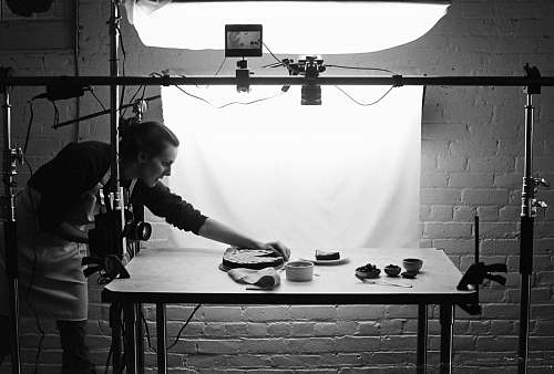 human grayscale photo of woman holding baking pan person