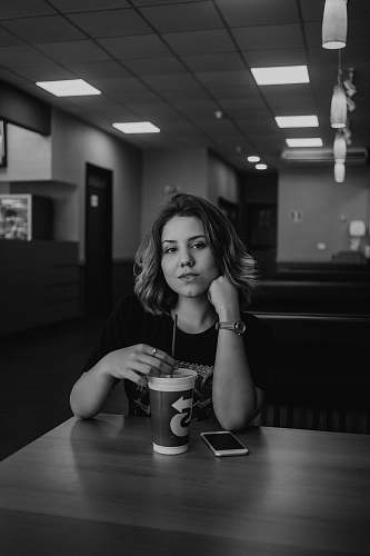 human grayscale photo of woman holding disposable cup with straw on table people