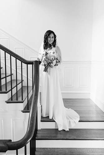 clothing grayscale photo of woman standing on stairs in wearing dress and smiling apparel