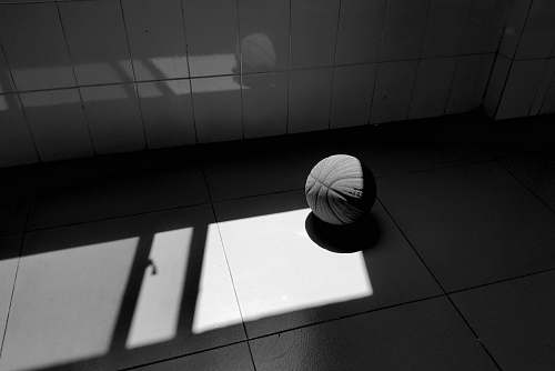 sphere grayscale photography of a basketball on the floor floor