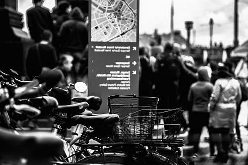 human grayscale photography of bikes near walking people people