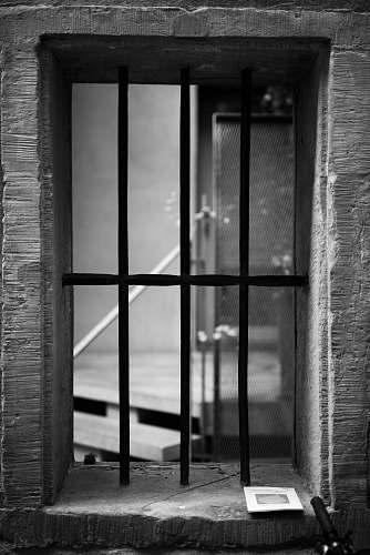 brick grayscale photography of black metal window window