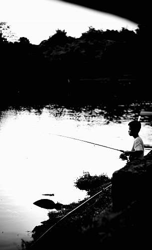 water grayscale photography of boy fishing on lake outdoors