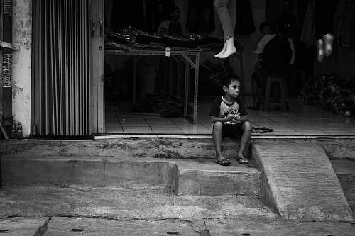 human grayscale photography of boy sitting on stairs person