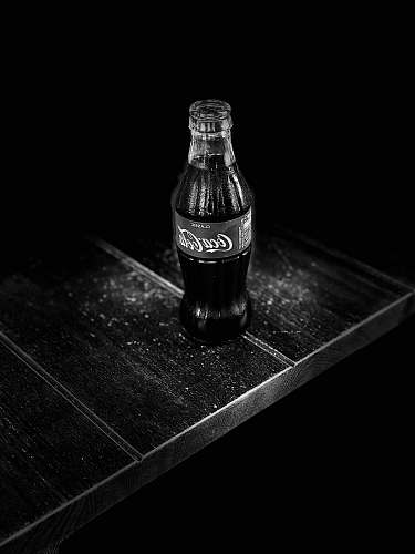 drink grayscale photography of Coca-Cola bottle on table coke