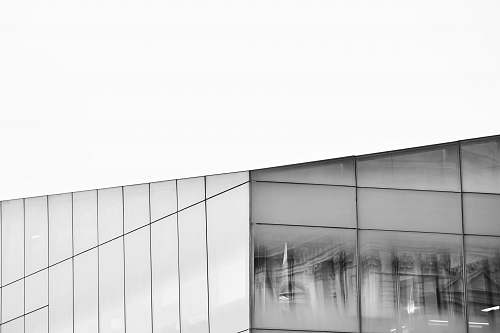 grey grayscale photography of glass building window reflection