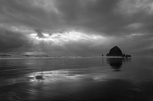 nature grayscale photography of island under clouds weather
