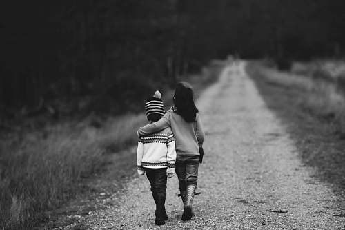 people grayscale photography of kids walking on road family