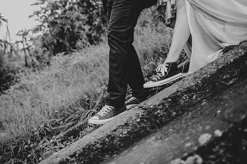converse grayscale photography of man and woman standing on ground wedding