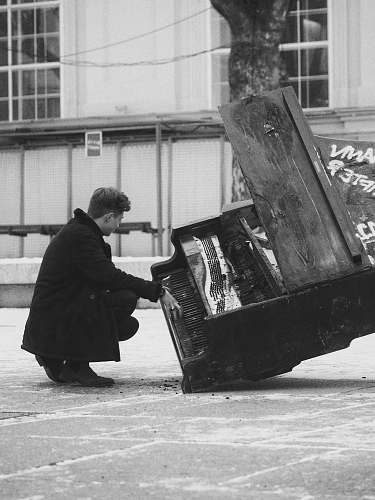 human grayscale photography of man crouching in front of damaged piano person