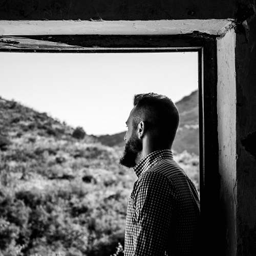 people grayscale photography of man in tattersall top looking outside of window person