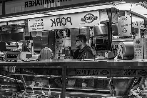 person grayscale photography of man inside pork food counter human