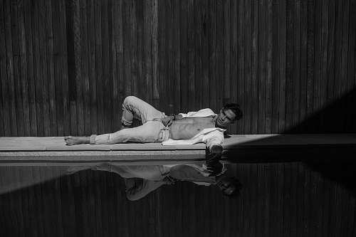 grey grayscale photography of man laying near swimming pool australia
