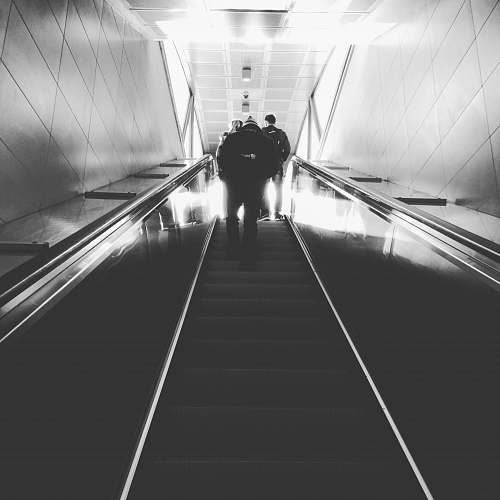tunnel grayscale photography of man on escalator people