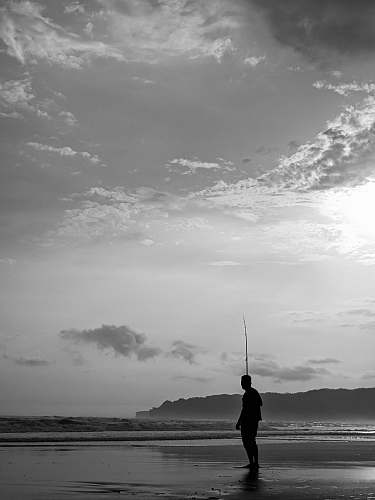 person grayscale photography of man on seashore grey