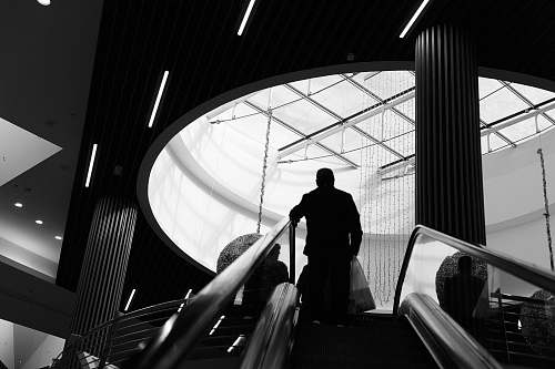 photo banister grayscale photography of man on stairs handrail free for commercial use images