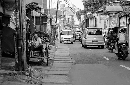 human grayscale photography of man sitting on chair near road street