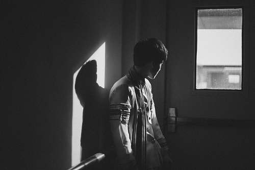 human grayscale photography of man standing beside door person