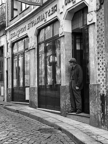 path grayscale photography of man standing on doorway walkway