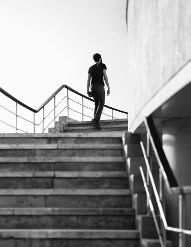 photo banister grayscale photography of man stepping on stairs handrail free for commercial use images
