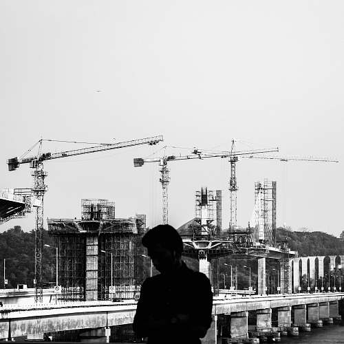 person grayscale photography of man with a construction site in the background human
