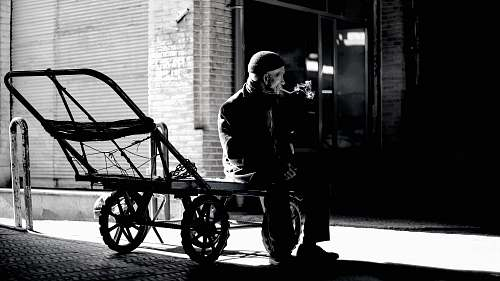 human grayscale photography of person sitting on trailer person