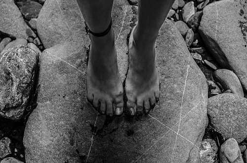 rock grayscale photography of person standing on rock albania