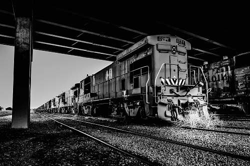 railway grayscale photography of train on station rail