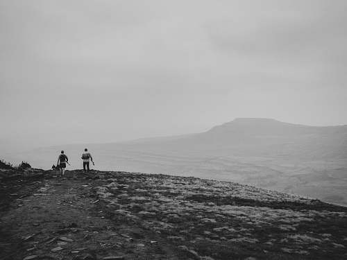 human grayscale photography of two people on cliff nature