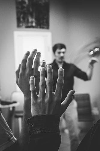 person grayscale photography of two people raising their hands finger