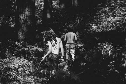 people grayscale photography of two topless persons standing at the forest during day human