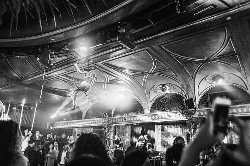 human grayscale photography of woman hanging near ceiling surrounded by crowd person