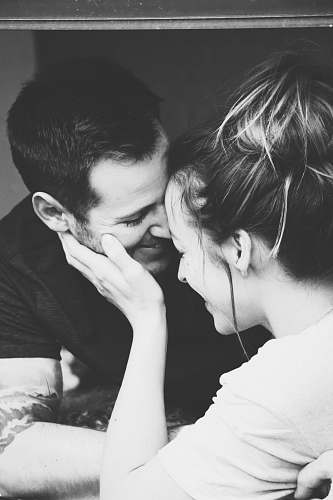 grey grayscale photography of woman holding man's face person