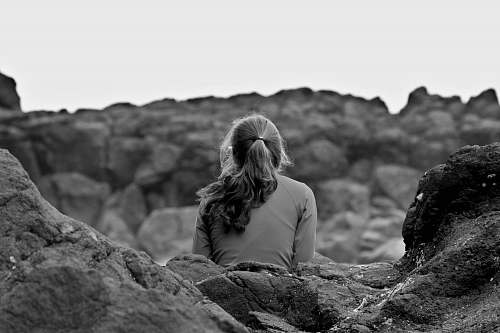 blonde grayscale photography of woman sitting on rock woman
