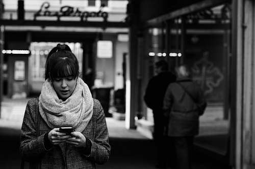 apparel grayscale photography of woman walking near street while using smartphone clothing