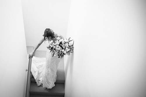 apparel grayscale photography of woman wearing wedding gown walking on steps clothing