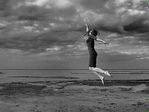 human graysclae photography of jumping woman near sea person