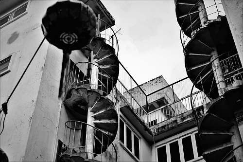 banister grey scale photography of spiral stairs beside building handrail