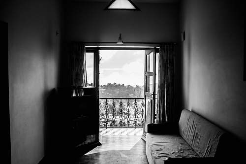 room greyscale photgraphy of fabric sofa beside wall inside the building kodaikanal
